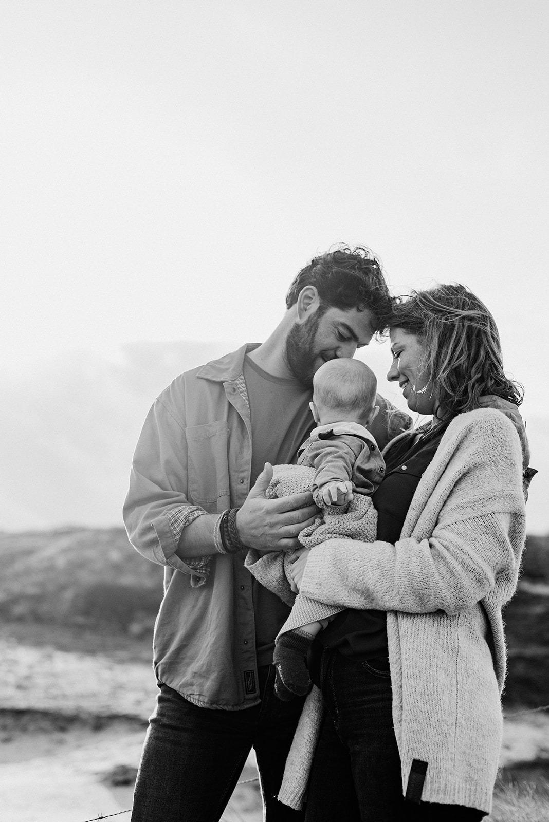 Papa en mama staan met hun zoontje in de duinen