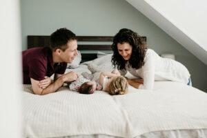 vader en moeder liggen op bed en kijken naar hun twee dochters