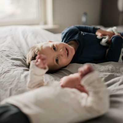 Grote broer speelt op bed