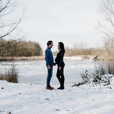 man en zwangere vrouw in de sneeuw