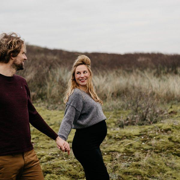 zwanger en samen lopen ze over de duinen